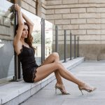 beautiful woman in the city in black dress sitting on the street with long legs and hiheels